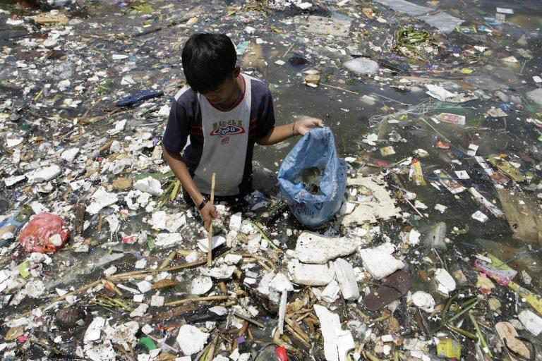A boy collects plastic near a polluted coastline to sell in Manila.jpg